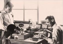 Sharp-Gründer Tokuji Hayakawa (rechts) beim Test von Radiogeräten Mitte der Zwanziger Jahre. Der Erfinder hatte zuvor einen stets scharfen, mechanischen Stift (daher der Firmenname Sharp) entwickelt und auf den Markt gebracht, ehe er das Geschäft als erster Anbieter von Radios in Japan auf den Elektronikbereich ausweitete (Bild: Sharp).