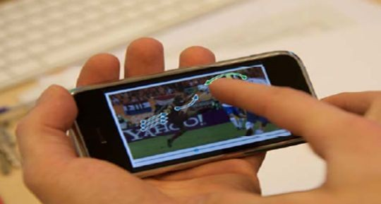 """Für das Betrachten von Videos entwickelten Forscher des Lehrstuhls Medieninformatik im Mobiltechnologie‐Exzellenzcluster UMIC an der RWTH Aachen mit """"DRAGON"""" eine neue Eingabetechnologie. Mit ihr dient der Bildschirm gleichzeitig zum Suchen im Video. Demonstriert wurde das am Videoclip eines Fußballspiels. Um die Stelle eines Handspiel‐Fouls zu finden, zieht der Sportfan den Ball auf dem Schirm zur Hand des verdächtigten Spielers - und das Video springt automatisch zur kritischen Position. Während der Benutzer die Objekte im Video bewegt, berechnet ein Server ständig die neue Position im Video und sendet diese praktisch ohne Verzögerung drahtlos zurück ans Mobiltelefon. Die Technologie gab es zwar schon auf leistungsstarken Desktop‐Computern, auf mobilen Geräten ist sie aber neu (Bild: RWTH Aachen)."""
