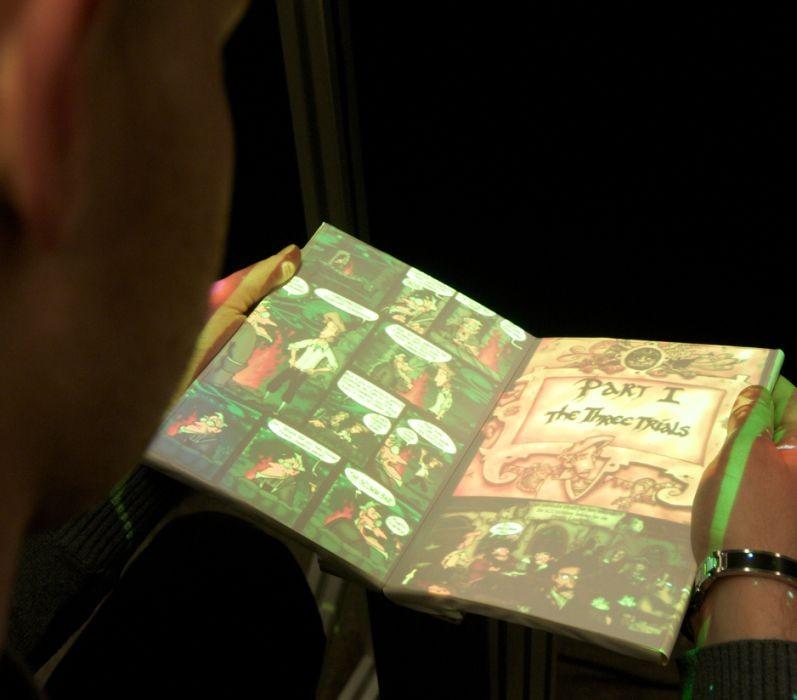 """Biegbare Displays in Handys und PDAs werden bald keine Besonderheit mehr sein. Der Lehrstuhl Medieninformatik an der RWTH Aachen entwickelt daher heute schon Eingabetechniken, um die Benutzung solcher Geräte einfacher zu machen. Eine davon ist TWEND. Sie zeigt, wie die Navigation in einem biegsamen E-Book der Zukunft aussehen könnte. Der wesentliche Teil des Prototypen sieht wie ein aufgeschlagenes Buch aus. Biegt man die oberen Ecken der linken oder rechten """"Seite"""" wie bei einem echten Buch, blättert man vor oder zurück: Man sieht, wie sich die projizierte Seite entsprechend bewegt. Wie bei einem echten Buch lässt sich auch das TWEND‐Buch schnell durchblättern, indem man eine der Seiten an der Außenkante nach hinten biegt. Dazu messen im Inneren sechs Sensoren, wie stark sich eine Seite verbiegt. Diese Daten werden live an einen Rechner gesendet, der Störungen herausfiltert und dann die Biegegeste identifiziert und ein passend animiertes Bild der Buchseiten an den Projektor schickt, der es von oben zurück auf das Buchmodell wirft (Bild: RWTH Aachen)."""
