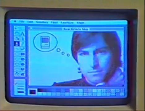 """Zwei Tage nachdem Apple mit seiner 1984-Werbung Geschichte geschrieben hat, betrat Jobs die Bühne um vor einer begeisterten Menge den Macintosh einzuführen. Schon damals genoss er die Rolle als Zeremonienmeister: Er holte den Rechner aus einer Tasche und zeigte eine Demo, die mit den Worten beginnt: \""""Macinstosh. Unglaublich gut.\"""" Nach einer kurzen Vorführung der Möglichkeiten wie Textverarbeitung, Schach und Grafik ? der Screenshot zeigt ein Beispiel -  spricht der Computer laut und sagte die Worte auf dem Bildschirm auf.<br />\""""Hallo, ich bin Macintosh. Es ist gut, aus dieser Tasche heraus zu sein. Ich bin an das öffentliche Sprechen nicht gewöhnt. Aber ich möchte, nachdem ich das erste Mal einen IBM-Mainframe gesehen habe, sagen: \'Traue keinem Computer, den Du nicht hochheben kannst.\' Offensichtlich kann ich sprechen, aber jetzt möchte ich mich zurücklehnen und zuhören. Mit Stolz möchte ich nun einen Mann einführen, der wie ein Vater zu mir war: Steve Jobs.\"""""""