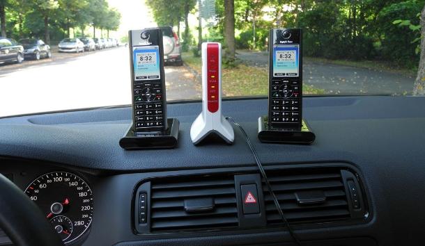 Die FRITZ!Box 6810 LTE mit Vodafone-SIM-Karte ist vertriebs-strategisch nur als stationäres DSL-Sprach-Daten-Ersatz-Produkt positioniert. In unserem Test funktionierte sie aber auch mobil im fahrenden Auto: Hier jedenfalls holt der rot-weiße LTE-Router 6810 mit Vodafone-SIM-Karte das Internet samt Telefonie über den LTE-Funk in das Auto und gibt die Sprache über DECT-Funk an die beiden schwarzen Schnurlos-Telefone AVM FRITZ!Fon MT-F weiter. Laptops dagegen werden über WLAN an den LTE-Router gekoppelt. Der LTE-Router hängt mangels Akku am 230-Volt-Anschluss des Autos, die beiden DECT-Telefone laufen in diesem Test auf Akku (Foto: Harald Karcher).