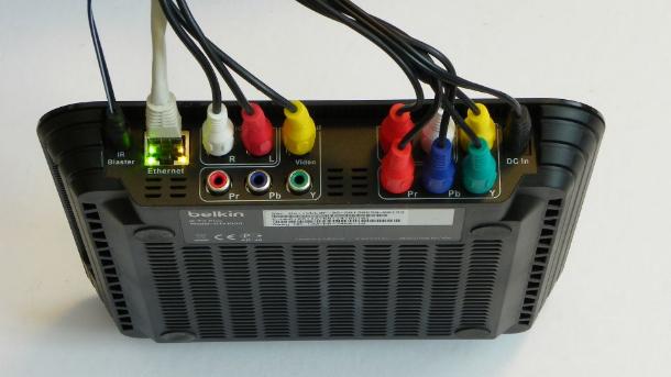 Der Sat-Receiver oder eine andere Eingangsquelle wird über mitgelieferte Cinch-Kabel an der rechten Seite neben der Stromversorgungsbuchse angeschlossen. Links daneben gibt es entsprechende Durchschleif-Ausgänge für einen Fernseher oder Monitor. Dann folgt eine Buchse fürs Netzwerk-Kabel und links außen eine kleine Klinkenbuchse fürs Kabel zu den beiden mitgelieferten Infrarot-Sendern (Bild: Peter Pernsteiner).