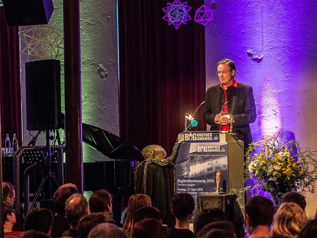 """Gestern Abend hat der Verein Digitalcourage e.V. in Bielefeld die """"Oscars der Datenkraken"""" verliehen. Der Negativ-Preis <a href=\""""https://bigbrotherawards.de/2015\"""" title=\""""BigBrowserAwards 2015\"""" target=\""""_blank\"""">BigBrotherAwards 2015</a> ging an Privatfirmen und an staatliche Organisationen. Im Bereich Arbeitswelt hat sich Amazon Logistik für den Preis qualifiziert.  In der Kategorie """"Behörden und Verwaltung"""" konnte der Bundesnachrichtendienst (BND) das Rennen für sich entscheiden, weil er laut Jury \""""aufs Engste in den menschenrechtswidrigen NSA-Überwachungsverbund verflochten ist.  Die Crowdworking-Plattformen Amazon Mechanical Turk und Elance-oDesk erhalten den Big Brother Award 2015 in der Kategorie Wirtschaft für die Umsetzung des \""""digitalen Tagelöhnertums\"""". Exemplarisch für die beständigen Versuche, den Bürgern gegen ihren Willen das Überwachungskonzept der Vorratsdatenspeicherung unterzujubeln, erhält der Ausdruck \""""Digitale Spurensicherung\"""" einen Neusprech-Award.  Das Bundesministerium für Gesundheit erhält den BBA 2015 in der Kategorie Verbraucherschutz. Bundesinnenminister Thomas de Maizière und Ex-Bundesinnenminister Hans-Peter Friedrich erhalten den BigBrotherAward 2015 in der Kategorie Politik für die systematische und grundlegende Sabotage der geplanten Europäischen Datenschutzgrundverordnung. <br> (Bild: Matthias Hornung CC 4.0)"""