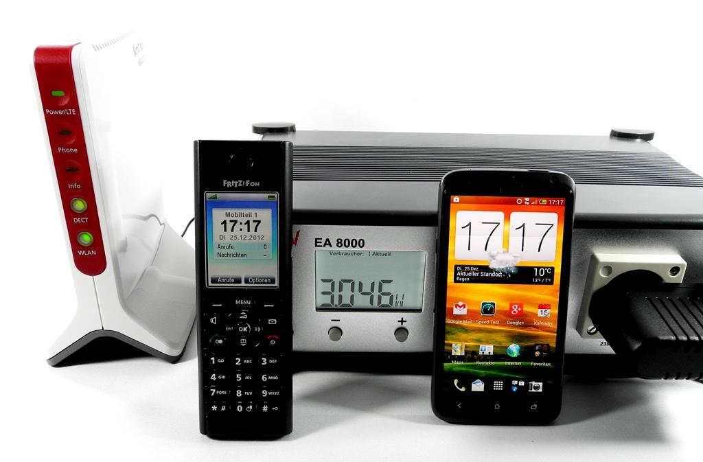 """Die Fritzbox 6842 LTE ist hier bereits mit dem schwarzen DECT-Handset und mit einem WLAN-Laptop in Lauerstellung verbunden. Dabei verbraucht die 6842 gut 3 Watt Strom. Sobald das """"HTC One XL"""" rechts im Bild die LTE-Fritzbox anruft, meldet der Strommesser """"ELV EA 8000"""" knapp 5 Watt Verbrauch. Zum Telefonieren schaltet das HTC-Handy übrigens gleich den 4G-Modus ab, die Fritzbox dagegen bleibt im LTE-Modus (Foto: Harald Karcher)."""