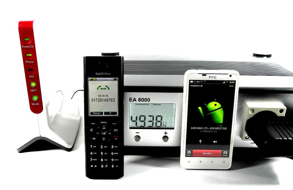 """Hier ist das weiße """"HTC Velocity 4G"""" mit der Vorwahl 0172 (Rechts) bereits mit dem schwarzen DECT-Handset (Mitte) der Fritzbox 6842 LTE (Links) mit der Berliner Vorwahl 030 am Standort München verbunden. Dabei geht der Stromverbrauch der 6842 von zuvor 3 Watt auf nunmehr fast 5 Watt hoch. Das weiße """"HTC Velocity 4G"""" schaltet zum Telefonieren den LTE-Modus vorübergehend ab, die Fritzbox aber nicht, denn sie nutzt bereits Voice-over-LTE von Vodafone (Foto: Harald Karcher)."""
