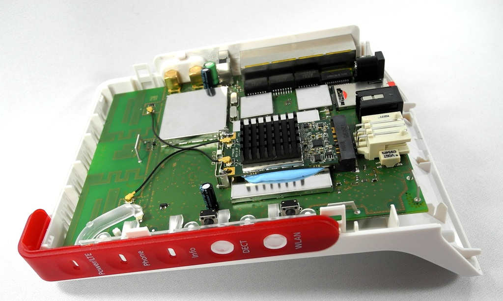 Mitten in der Fritzbox 6842 LTE sitzt, unter den schwarzen Kühlrippen, das LTE-Mobilfunk-Modul für 800, 1800 und 2600 MHz. Rechts daneben sitzt die cremefarbene TAE-Buchse für analoge Telefone. So schlägt die Fritzbox eine weite Brücke zwischen ganz alter und ganz neuer Telefon-Technik (Foto: Harald Karcher).