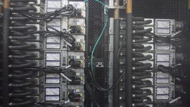 Die Rückseite eines Racks hat normalerweise wenig Aufregendes zu bieten. Beim SuperMUc spielt aber genau hier die Musik: Neben den Netzteilen (links) ist die Zuleitung für das Wasser zu erkennen, das darüber bis dahin gebracht wird, wo die Wärme entsteht: an Prozessoren und Hauptspeicher (Bild: ZDNet).