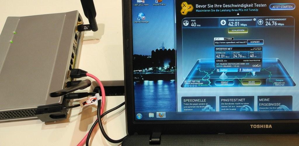 """Auf der CeBIT 2012 demonstrierte die Deutsche Telekom den LTE-Business Router """"LANCOM 1781-4G"""" auf Ihrem rappelvollen LTE-1800-Messe-Stand. Über ein magenta-farbenes LAN-Kabel war der LTE-Router mit einem Toshiba-Windows-Laptop verbunden. Ein kompetenter Techniker, der das LTE-Messe-Netz auch selber konfigurierte, demonstrierte hier gerade Messwerte von 42 MBit/s im Download und fast 25 MBit/s im Upload über das Messtool Speedtest.net (Foto: Harald Karcher). <br> <a href=\""""http://www.zdnet.de/88132147/lte-warum-kommen-keine-100-mbits-einflussfaktoren-der-4g-surfgeschwindigkeit/\"""" title=\""""Zum Artikel: LTE: Warum kommen keine 100 Megabit/s?\"""">Zum Artikel: LTE: Warum kommen keine 100 Megabit/s?</a>"""